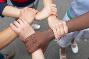 Diverse people holding each other's arms