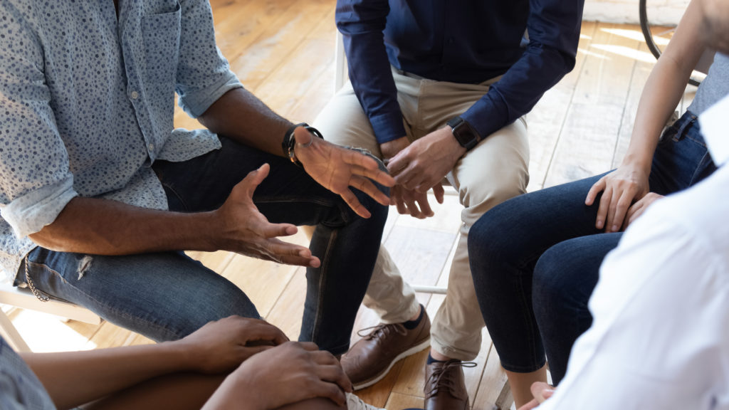 Diverse group of people sitting in a circle talking